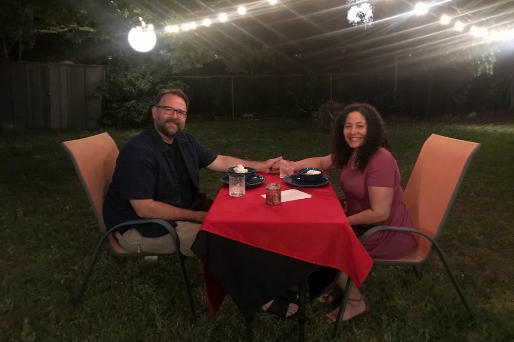 A couple hold hands as they enjoy dinner in their backyard.