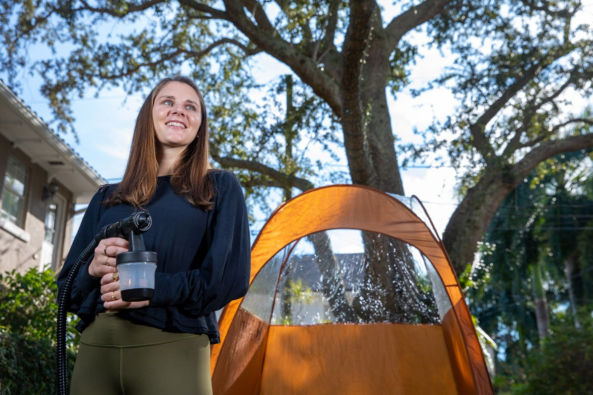 A college student stands with her sunless spray tan kit in her backyard.